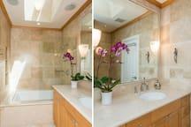 2 views of bathroom  that has skylight over tub.