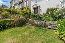 Front yard that is terraced with steps down to Castro Street.