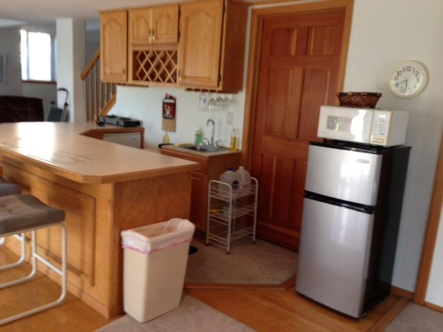 Kitchenette with frig, microwave, bar sink, 2 burner hot plate, coffee maker, toaster and cupboards with dishes, utensils, and cookware.