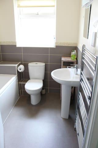 New modern bathroom with bath and shower over bath newly
