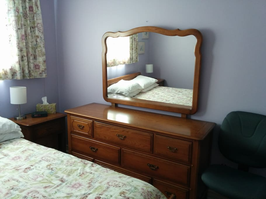 Purple room has a triple dresser with mirror and a chair.