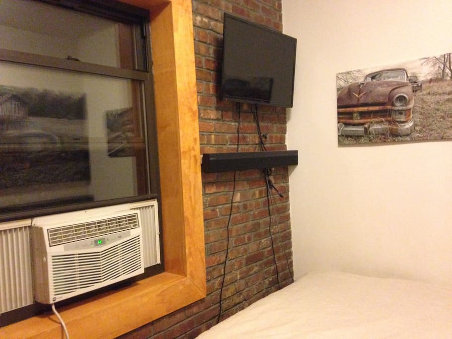 tv on brick wall and air conditioning