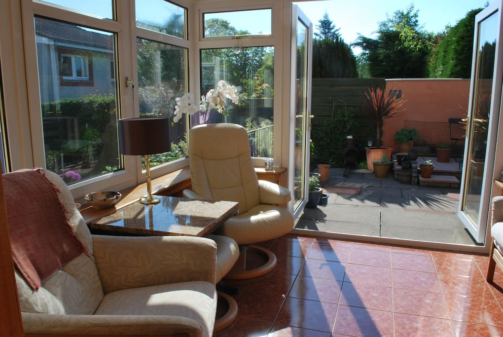Large, sun-bathed conservatory with doors to patio