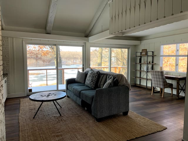Living room features ample seating and includes TV and amazing views of the lake with a back deck, while seamlessly connecting to dining area and kitchen in this open design.