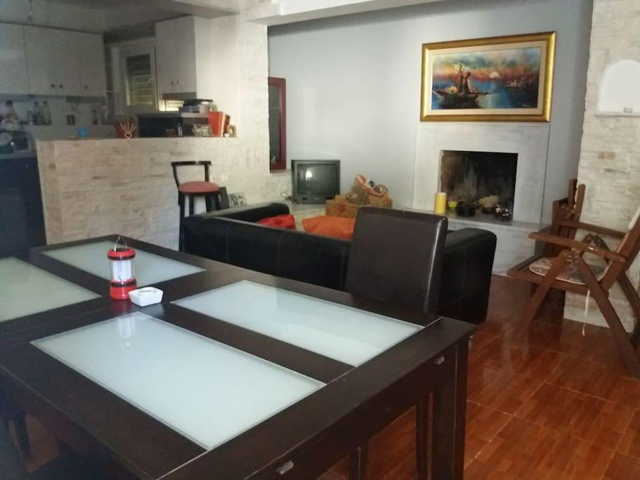 Σαλόνι - τραπεζαρία - κουζίνα (ενιαίος χώρος), με καναπέ κρεβάτι και τζάκι.