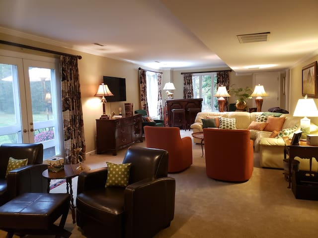 """Great room with leather sofa , swival chairs, 55"""" smart TV, fireplace, bar with microwave, coffee pot and mini refridge."""