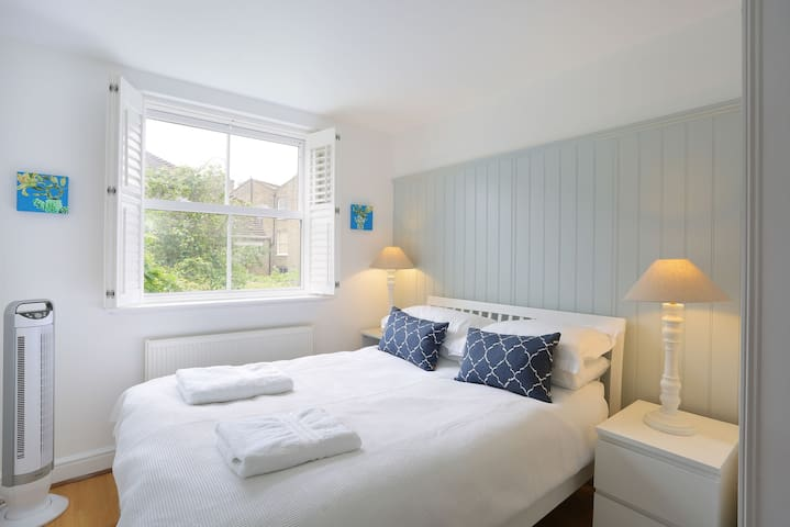Upstairs bedroom; Uk size double bed. Plug in aircon unit. White shutters.