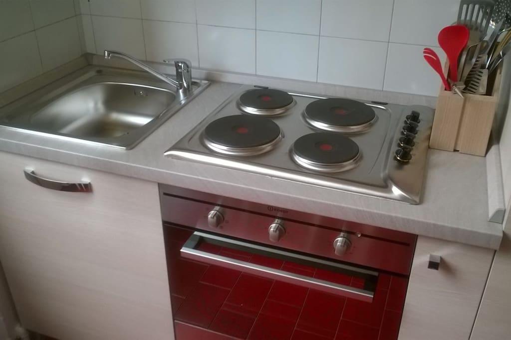 angolo cottura con fuochi, forno e frigo