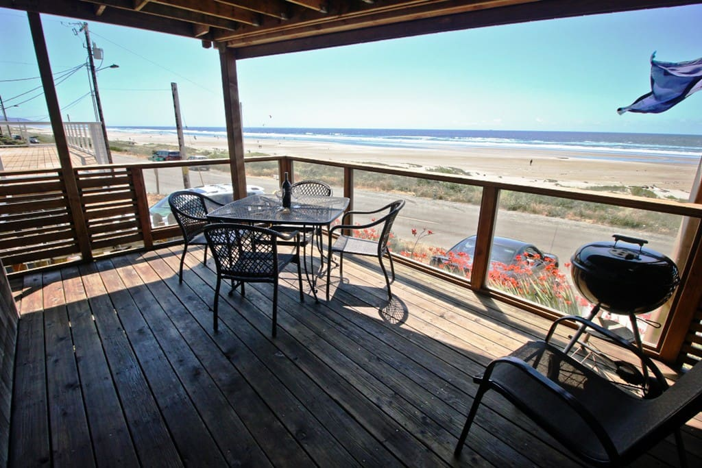 Lower covered, glassed deck with a patio table for 4, charcoal BBQ and spectacular coastal ocean views