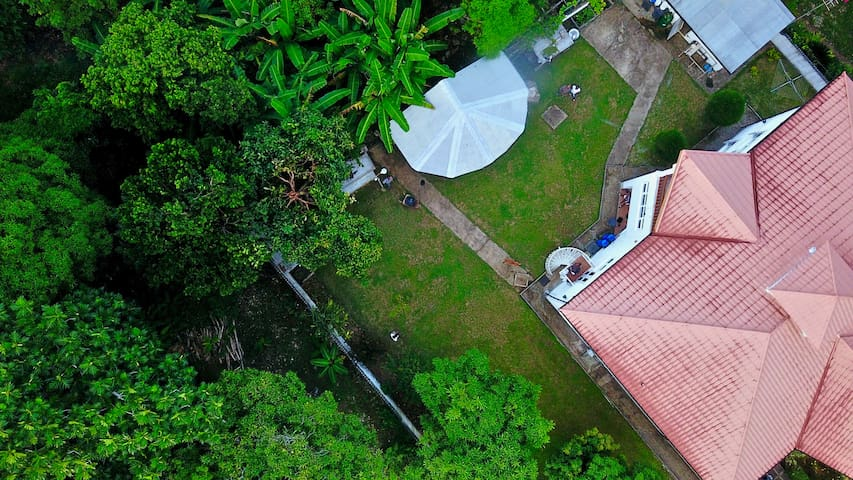 Arial view of the rear of the house, showing the covered BBQ station which is available for you for  cook your Jerk Chicken! The spiral staircase is our access to the yard, to the right you have your own access/small veranda opening onto the garden.