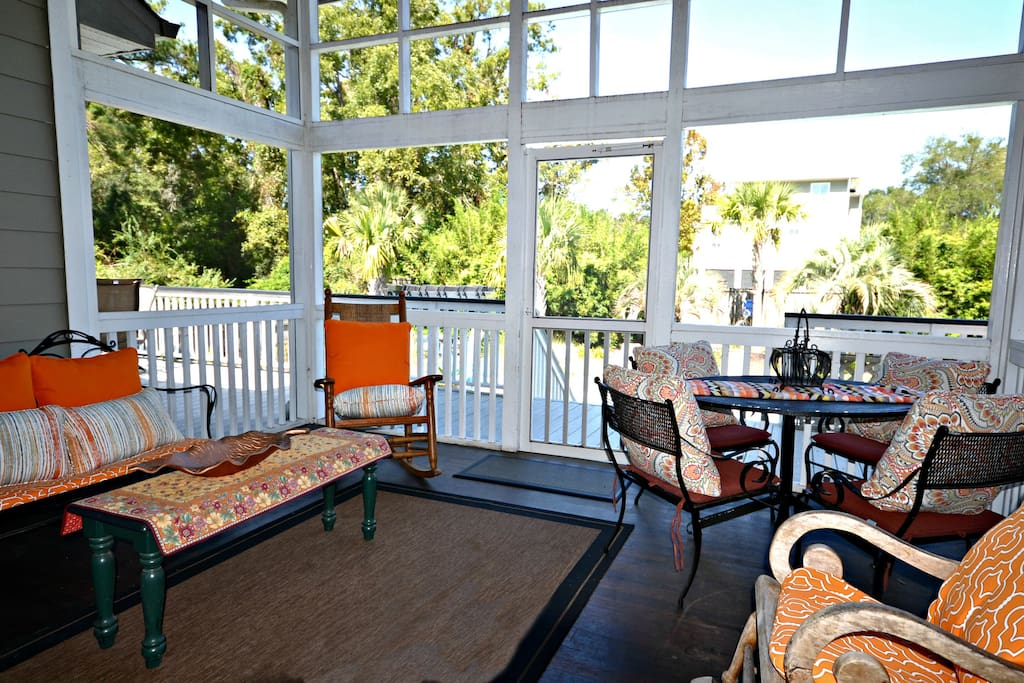 Great screened porch in back overlooking deck and pool with ceiling fan. Seating and tables.