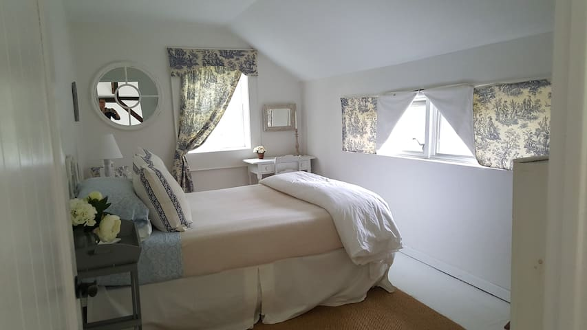 Upstairs bedroom - Queen bed - located next to bath/shower room, overlooking garden and deck. A calm, fresh space to rest and relax. Desk and chair. Closet and shelving.  Natural sisal rug on white, painted floorboards. Overlooking deck and garden.