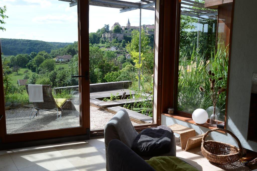Salon avec cheminée, vitré avec porte coulissante, à côté du bassin et vue sur Frôlois