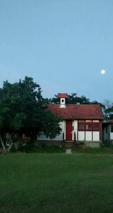Entrada da casa com lua cheia no céu.
