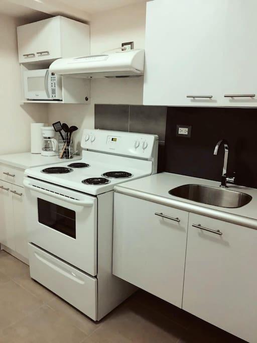 Cocina equipada con refrigeradora estufa, horno microondas,cafetera y, vajilla y trastos de cocina.