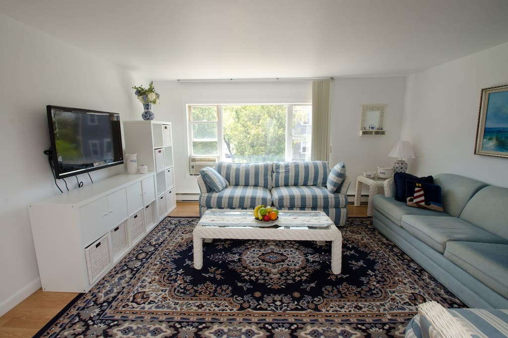 large bright living room with flatscreen tv and plenty of seating