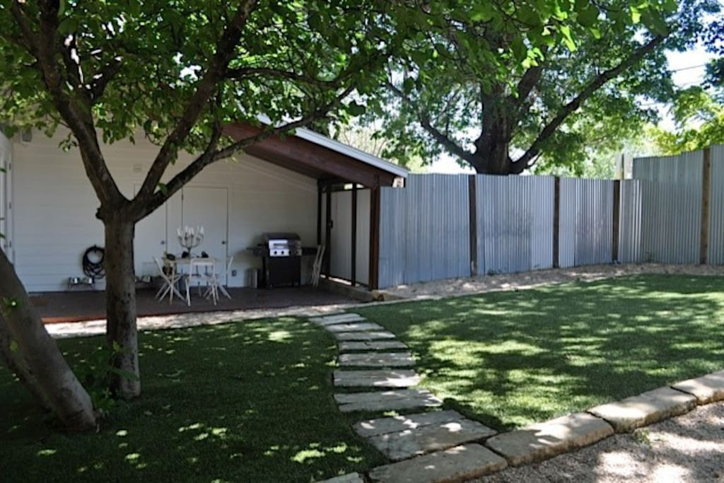 This is the view from the front of the guest house which shows the entrance guests use and pathway to front porch. Note privacy fence.
