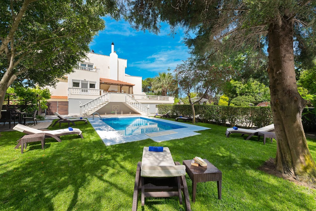 Garden and swimming pool area with stylish sunbeds with  comfortable cushions and pool towels  on the lawn grass enjoying the shade of trees and relax .