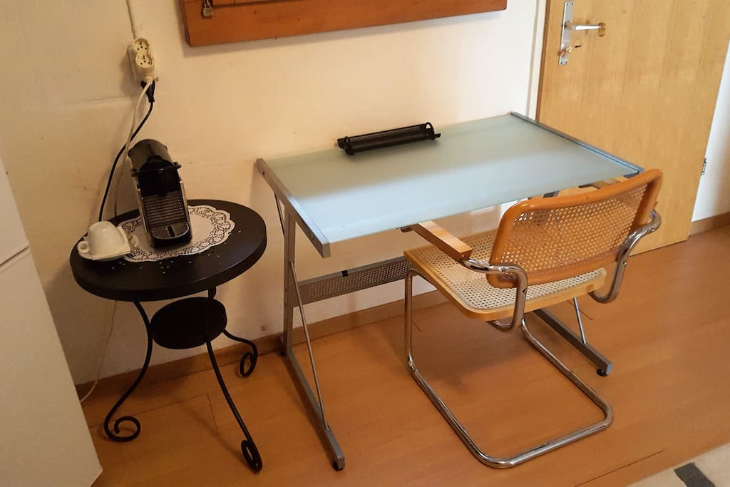 Im Wohnbereich steht ein Tisch für Laptops, Büroarbeiten, etc. Daneben die Nespresso-Maschine.