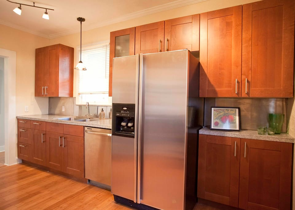 Fully-stocked kitchen with stainless steel appliances, convection oven, and gas stove.