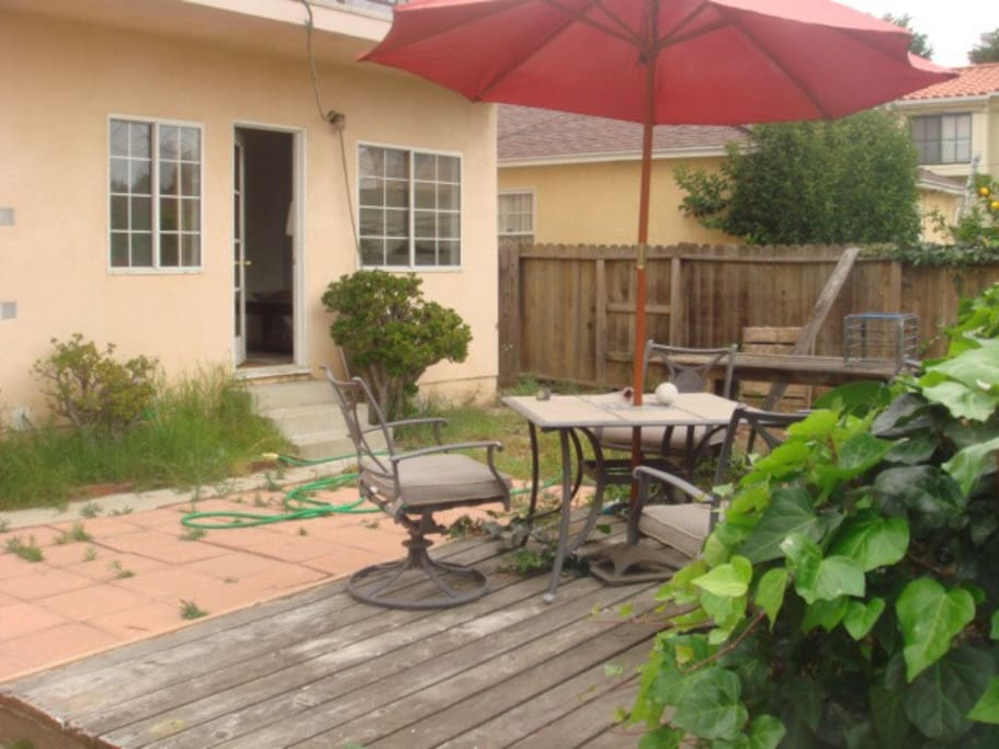Separate entrance to apartment; wooden deck sitting area.