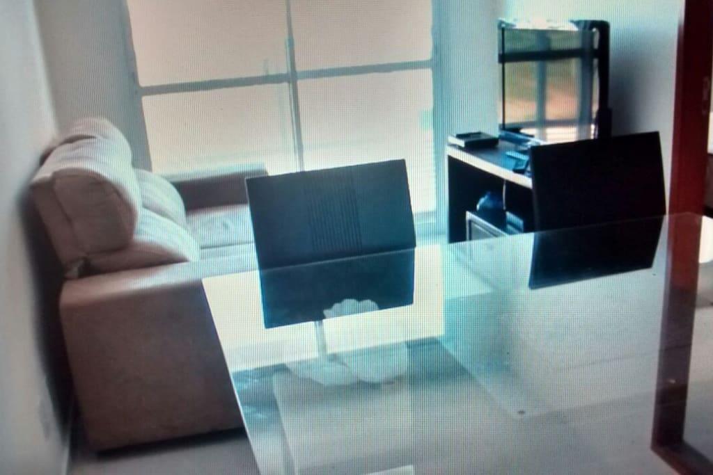 Sala com sofá e TV Digital.