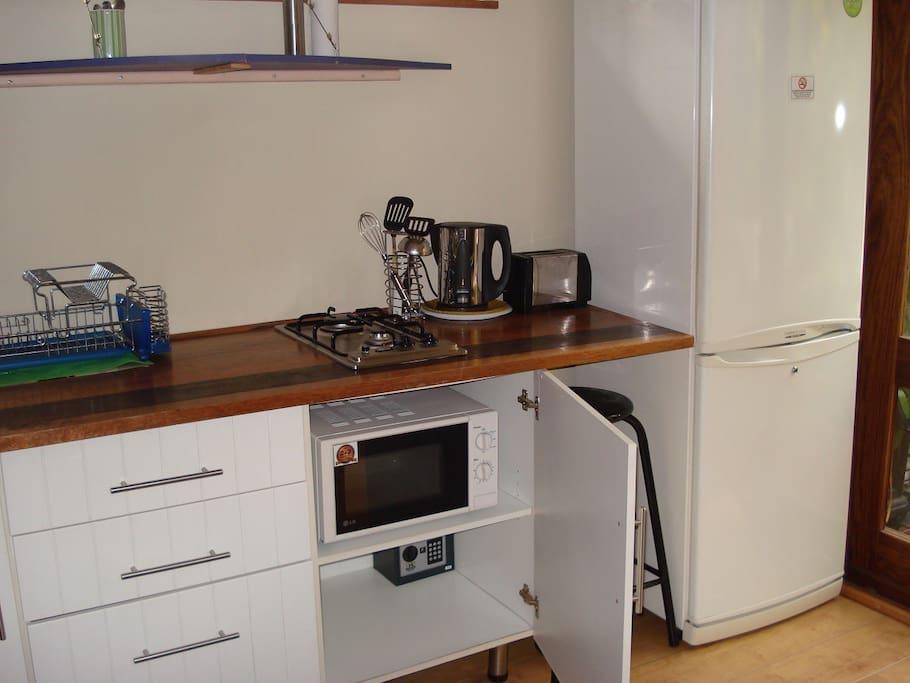 Kitchenette with big fridge, 2 plate gas hob, microwave hidden away, prep bowl, kettle, toaster, etc