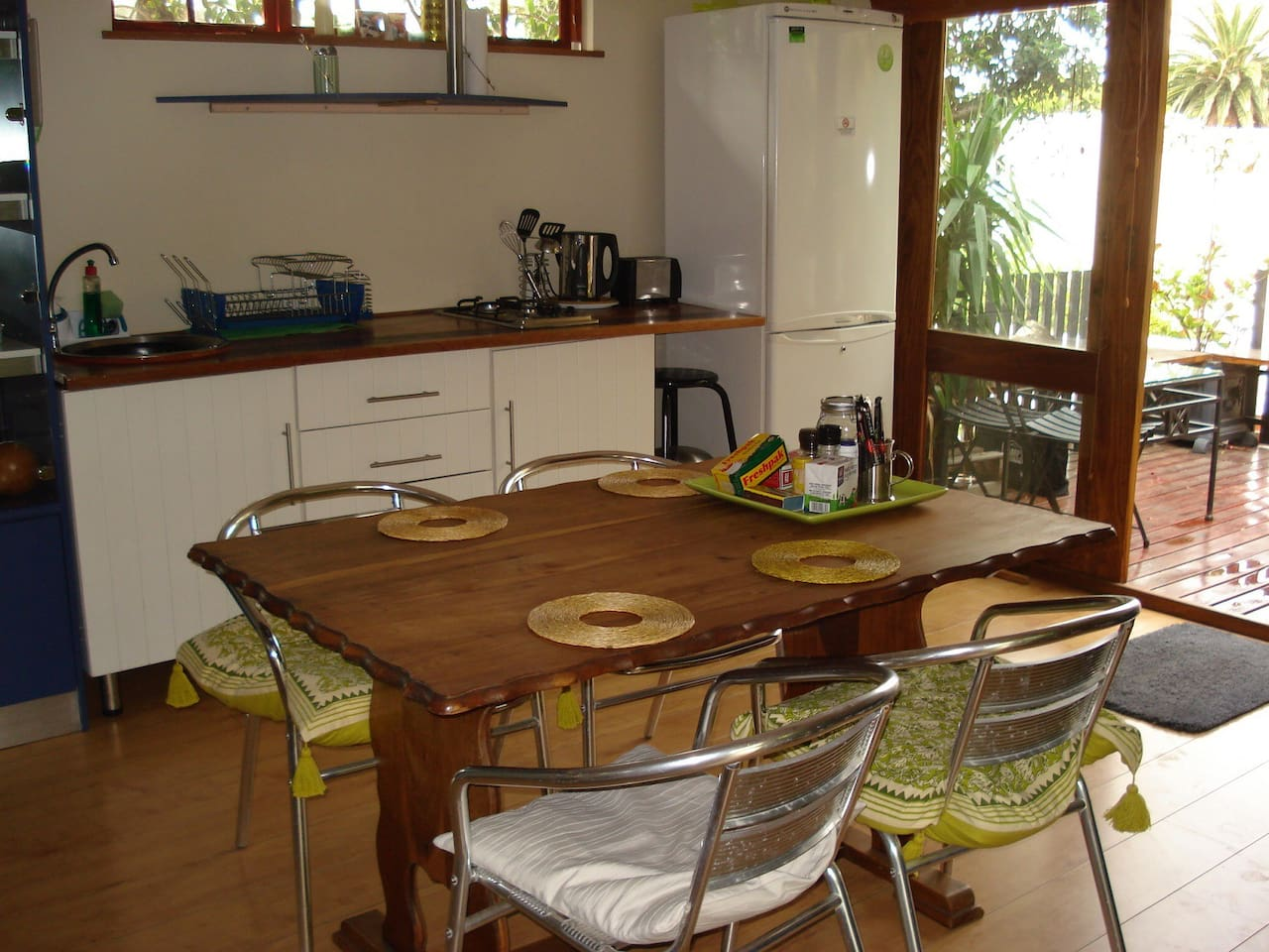 Kitchen area opening up to deck:  large fridge, table with 4 chairs, 2 plate gas hob and microwave