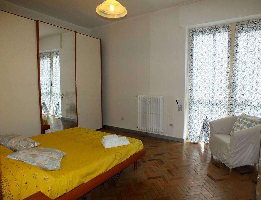 Camera da letto ampia e spaziosa con letto matrimoniale e poltrona di disimpegno