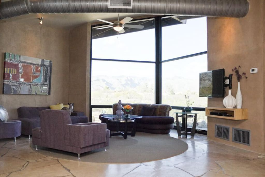 The living room with flat screen TV and floor to ceiling windows