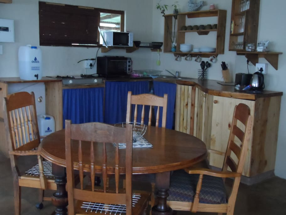 Kitchen area with fridge, cooker top and microwave, cutlery and crockery for 4 people