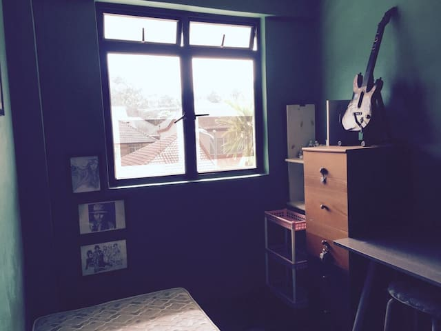 Window facing the road. Shelves and drawers to the right.
