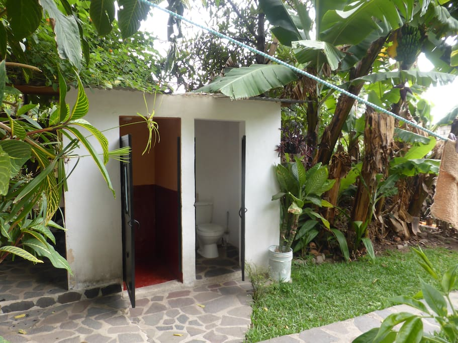 Hot  shower and toilet room next to the banana trees