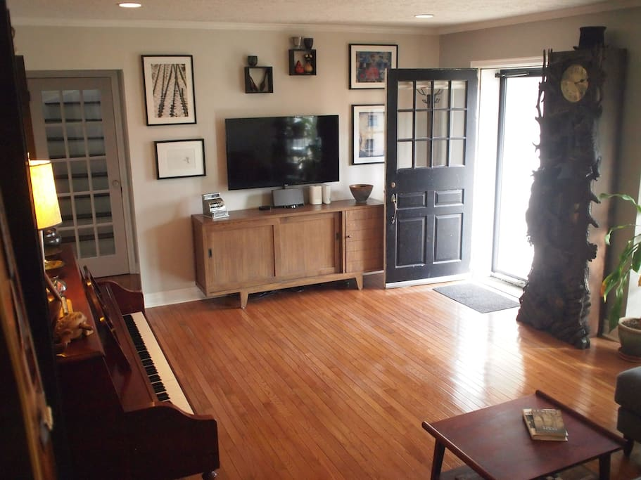 Living room equipped with streaming media smart TV & beautiful upright piano.