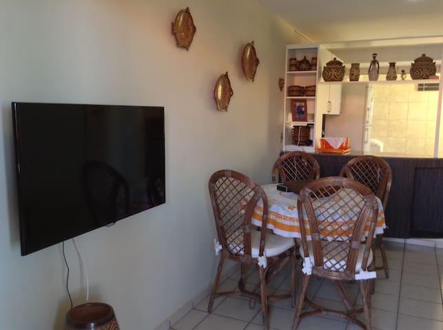 Sala TV e mesa de jantar.