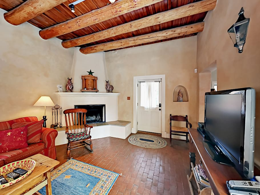 The charming condo is crafted with authentic brick floors and vigas ceiling beams.
