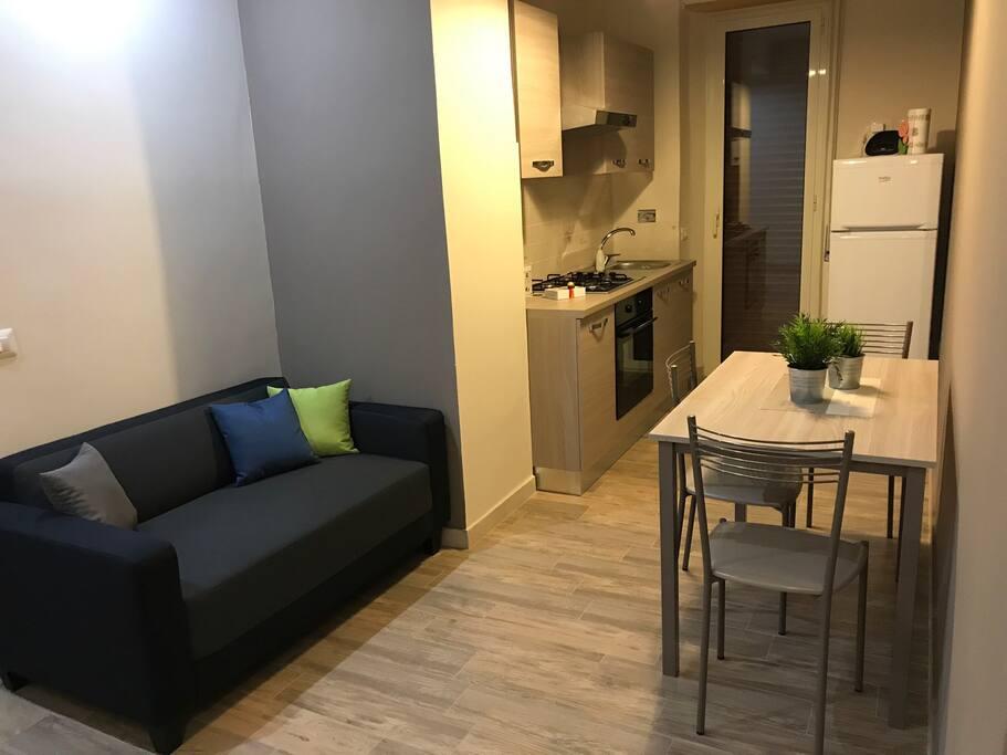 Zona living con cucina e macchina del caffè espresso.