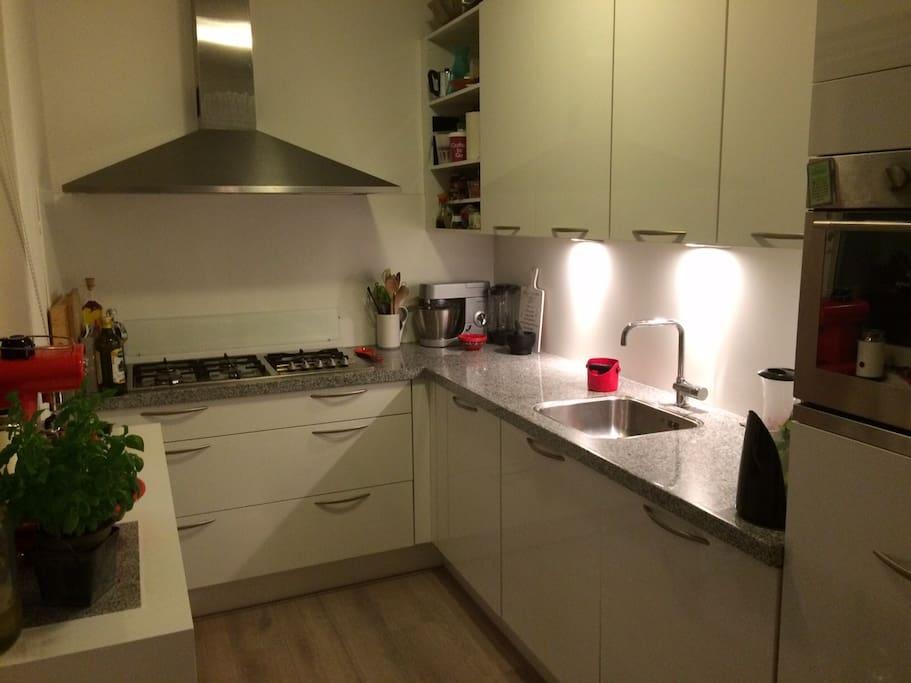 Keuken (inclusief espressoapparaat). Vanuit de keuken gaat een deur naar de tuin (16m2) waar ook een bbq staat die gebruikt kan worden.