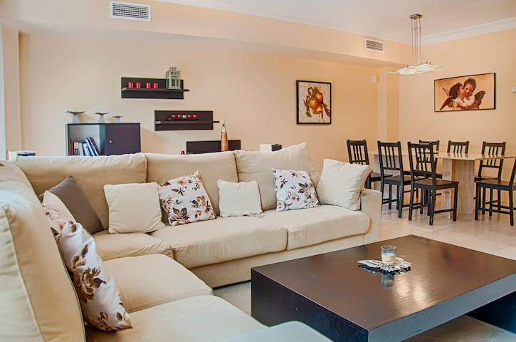 Ample living room with cosy sofa and dining room with marble table table