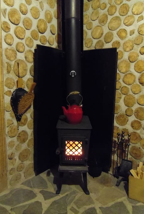 Modern cast iron woodstove from Norway looks traditional, operates easily, and heats cabin efficiently.