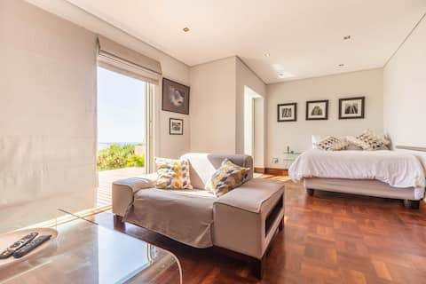 Modern studio in Camps Bay with deck and sea view.