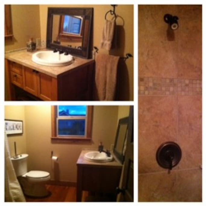 Adjacent rustic bathroom includes toiletries and decorative tiled shower with rubbed bronze fixtures.