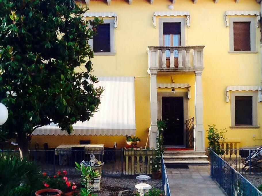 Entrata principale della casa con il suo giardino ricco di colori.