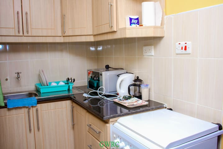 Spacious Kitchenet with microwave,  electric kettle,  gas cooker, and basic supplies of tea bags, coffee,  water, and soda