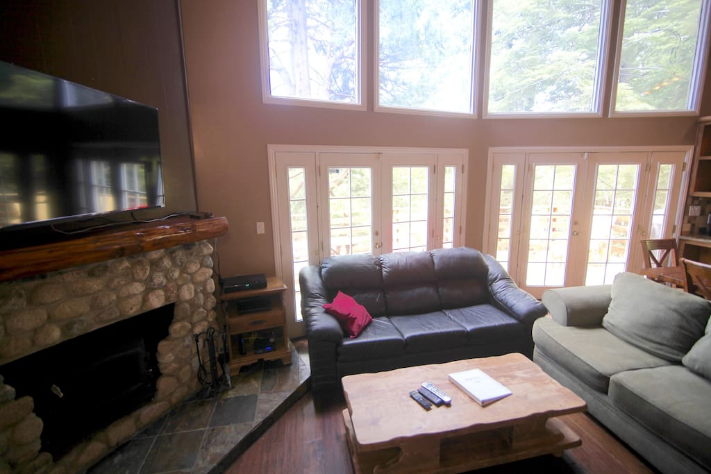 Two sofas, flat screen TV and wood burning fireplace in living room