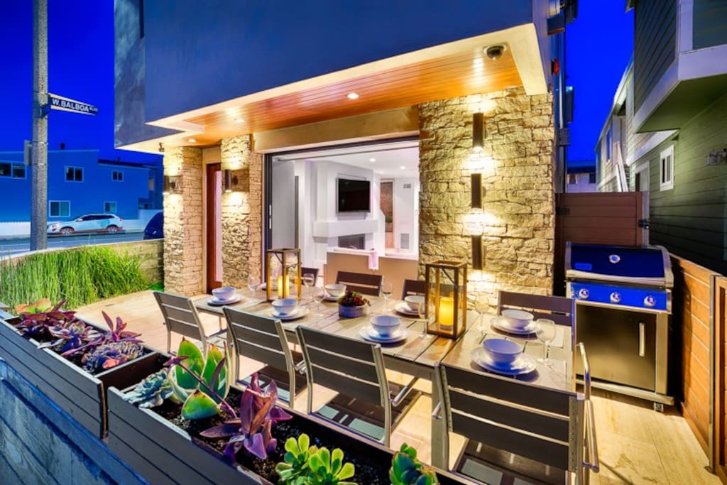 Front patio seating for 8 with grill and modern lighting.
