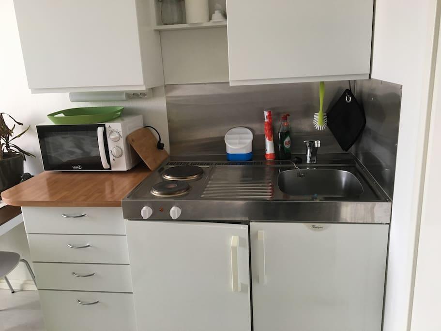 Keittonurkkaus: keittolevyt, jääkaappi, kahvinkeitin ja mikroaaltouuni.