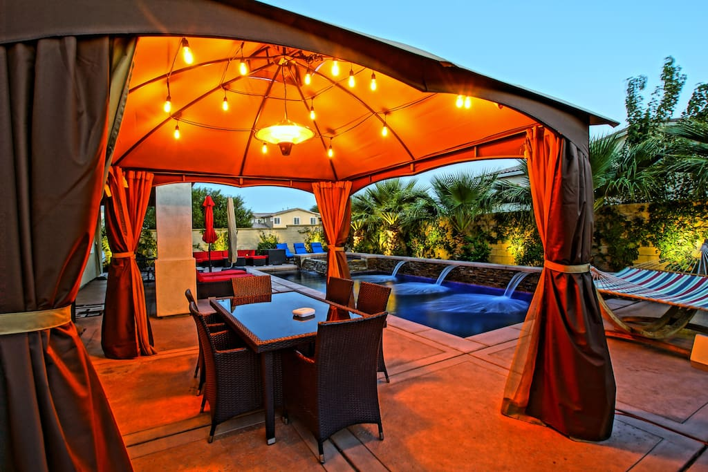Resort Style Living - Covered outdoor Dining with string lights and hanging latern heater