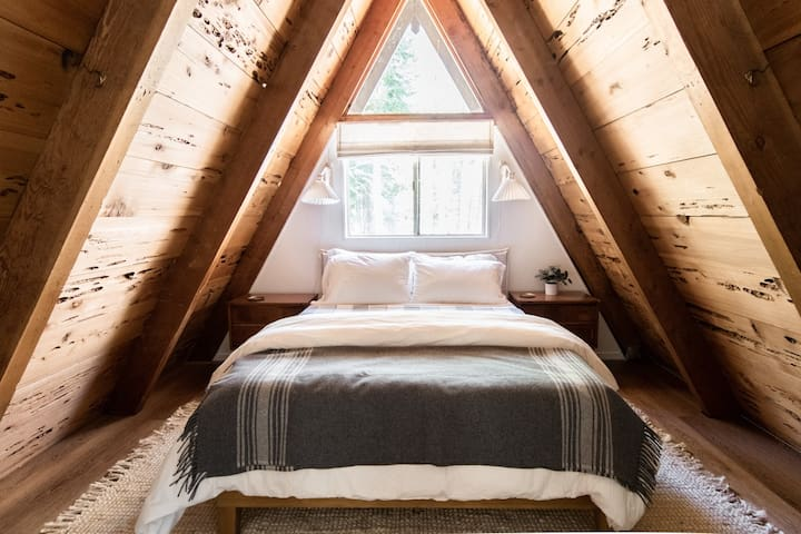 Upstairs bedroom — Queen bed sleeps two guests. Adaptive foam mattress, luxurious linens, and Pendleton wool blankets.