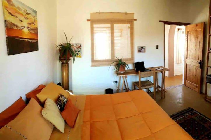 Dormitorio con cama de 2 plazas, pequeño escritorio y estantería para disponer enseres.